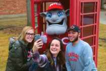 Big Red and students taking a selfie in the phone booth.