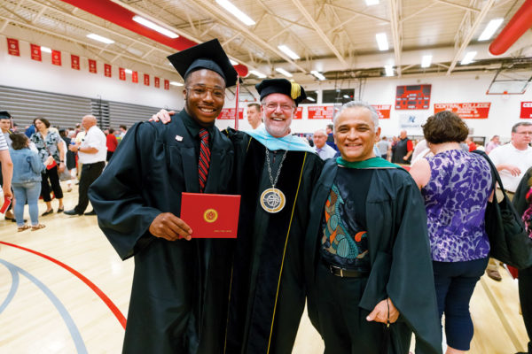 President Mark Putnam, center, and Associate Professor of Music Gabriel Espinosa congratulate Jeremy Vester '19 following graduation.