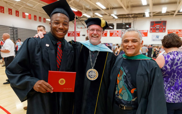 President Mark Putnam, center, and Associate Professor of Music Gabriel Espinosa '79 congratulate Jeremy Vester '19 following graduation.