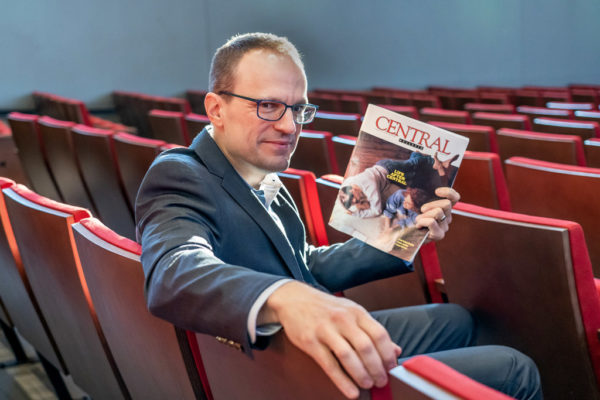 "Kyle Munson '94 sits in Douwstra Auditorium holding the Spring 1994 issue of Central Bulletin, then the alumni magazine. As a senior, Munson wrote an editorial titled ""Now What?"""