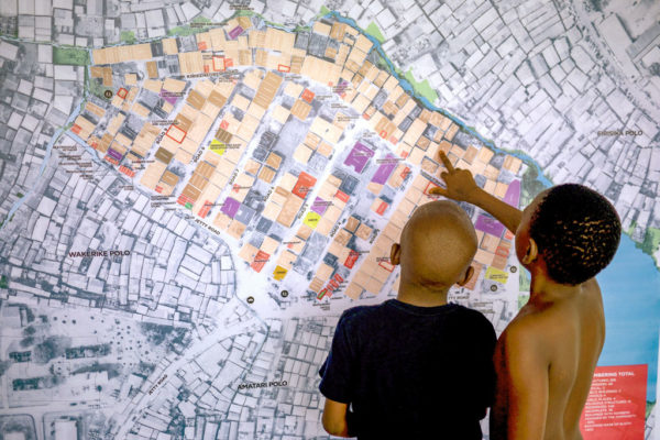 Two children who reside in an urban neighborhood find their home on a Cadasta map.