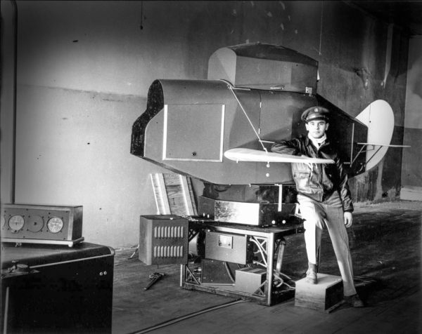 Flight instructor Paul Metcalf poses with an early flight simulator — called a Link trainer — used in Central's ground school instruction.