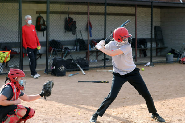 The 2020-21 season is unlike any of the 36 campaigns that preceded it for Central's NFCA Hall of Fame Coach George Wares '76, who watches a masked Taryn Hintz '24 take a cut in a small-group fall practice.