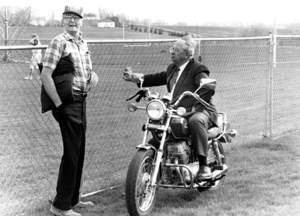 President Emeritus Ken Weller leans his motorcycle against the fence while watching a softball game following his retirement.
